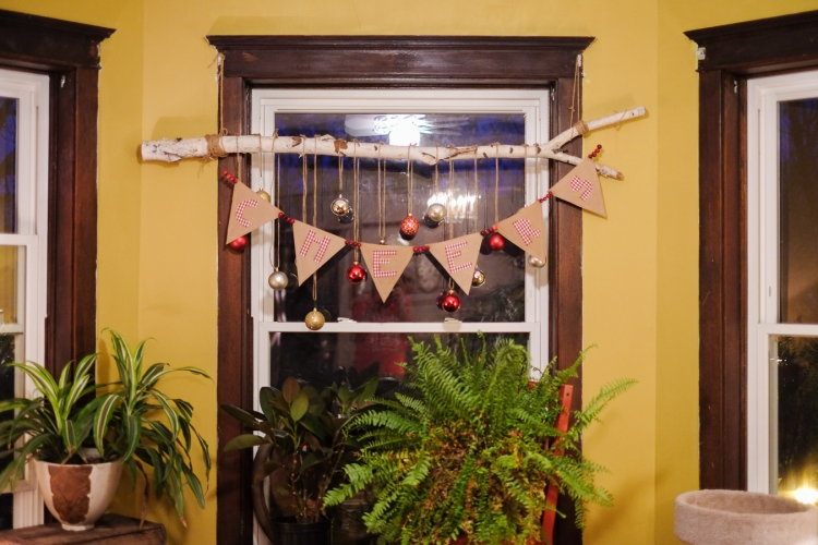 Hang banner! You can choose an open wall, doorway, window, mantle, or buffet/hutch. We hung ours on a birch branch suspended in front of a bay window and accentuated it with hanging sparkly ornaments.